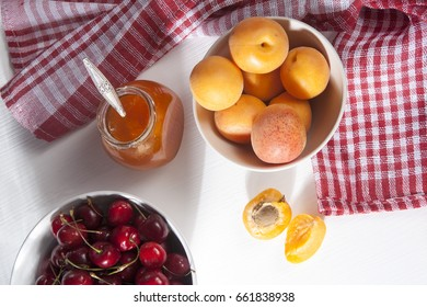 Apricots in a bowl and jam in a jar on a white table with a red and white towel, handmade summer blanks