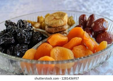 Apricots, Dates, Raisins, Prunes, Figs in a glass tray. Israeli mix of dried fruits - symbols of Jewish holiday Tu Bishvat