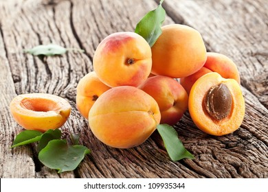 Apricots fruit with apricot leaves on the old wooden table.