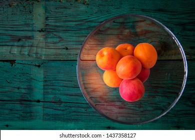 apricots in glass bowl on wooden background
