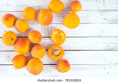 Apricots. Ripe fresh apricots on a wooden white background, top view, space for text.