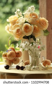 Apricots and tea roses on the table in the summer garden
