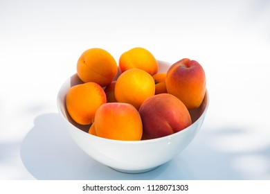 Apricots in a white bowl on white background