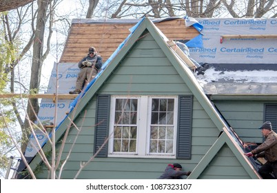 April 1 2018 Michigan USA; workers re shingle and repair  a home with a very steep pitch