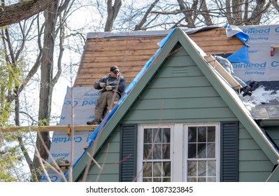 April 1 2018 Michigan USA; workers fix a roof on a house with a very steep pitch