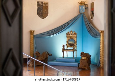 April 10, 2009, Pubol, Spain. Gala Dalí Castle House-Museum. Dali's throne in the throne room of the castle. Next to the gilded armchair are lions guarding, behind them a blue drapery.