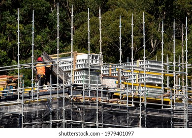 April 10, 2021. Worker assembling ply floor formwork and PVC concrete wall formwork on the top floor of new unit block at 56-58 Beane St. Gosford, Australia. Part of a series.