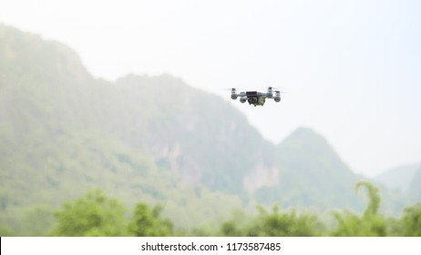 April 11, 2018 at 1:13 AM, Lampang [Ngao] Thailand Small Smart Drone quadrocopter Flying on White Sky in the Rainy Day and Beautiful Mountain Green Trees on Background.