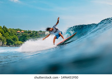 April 11, 2019. Bali, Indonesia. Indonesian surfer ride on surfboard at ocean wave.