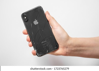 April 11, 2020, Rostov-on-Don, Russia: human hand holds smartphone iPhone X of space grey color with accidentally broken back glass on white background, front view.