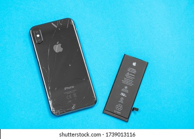 April 11, 2020, Rostov-on-Don, Russia: Lithium ion black battery from Apple iPhone X and smartphone on a blue background. Replacing the old damaged battery in your smartphone.