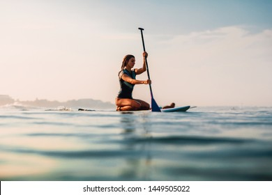 April 12, 2019. Bali, Indonesia. Stand Up Paddle surf girl in ocean. Stand Up Paddle surfing in Bali