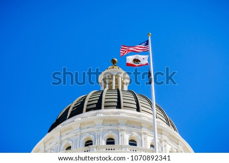 April 14, 2018 Sacramento / CA / USA - The US and the California state flag waving in the wind in front of the dome of the California State Capitol