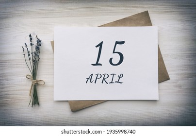 April 15. 15th day of the month, calendar date.White blank of paper with a brown envelope, dry bouquet of lavender flowers on a wooden background.  Spring month, day of the year concept.