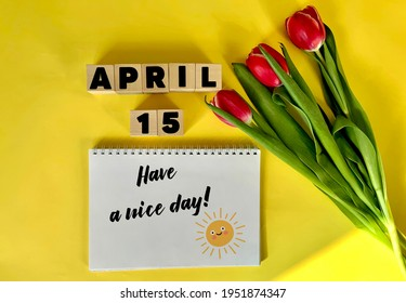 April 15 on wooden cubes on a yellow background.Next to a bouquet of tulips and a notebook with the inscription have a nice day .Calendar for April .