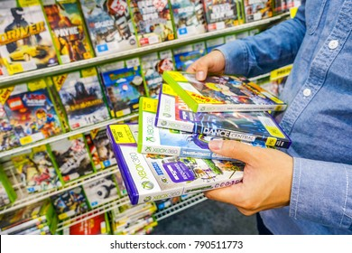 April 15th 2017, man holding several old preowned Xbox 360 games at front of a shelf full of games in a shop. Wagga Wagga, NSW Australia.