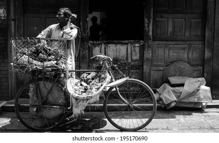 April 16, 2010 Kathmandu, Nepal. A fruit Merchant with his bicycle basket full of fruit waiting for a customer to buy. Black and White photo makes it more dramatic.