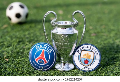 April 16, 2021 Moscow, Russia. The UEFA Champions League Cup and the emblems of the football clubs Paris Saint-Germain F. C. and Manchester City F. C. on the green grass of the lawn.