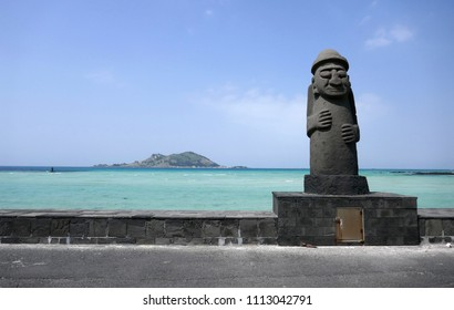 APRIL 17, 2018 : Dol hareubang ancient stone statue in front of a turquoise sea with volcanic island, Jeju Island, South Korea.