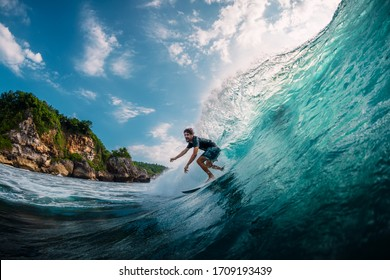 April 17, 2019. Bali, Indonesia. Surfer ride on surfboard at barrel wave. Professional surfing in ocean