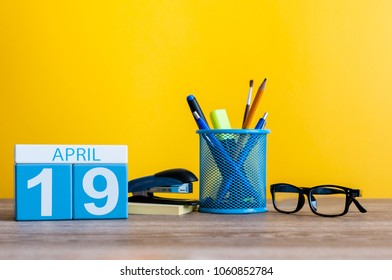 April 19th. Day 19 of month, calendar on business office table, workplace with yellow background. Spring time