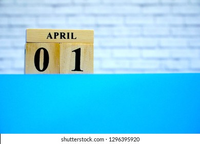 April 1st. Wood block calendar on blue table, white brick wall background. Spring day, Free space for any text design. All Fool's Day.