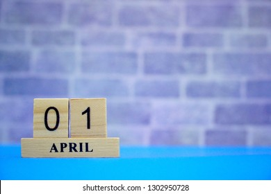 April 1st. Wood block calendar on blue table, brick wall background. Spring day, Free space for any text design. Fool's Day. Can be use decorate for any advertising, brochure.
