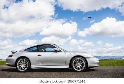 April 2, 2018 Eugene Oregon - A silver Porsche 911 body style 996 sits on an empty road under a sunny cloud filled sky near some green fields of grass.