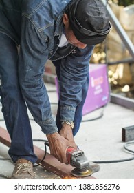 April  20, 2019 :  Bangkok,Thailand A man  is going to  industrial metal grinder to grind down stainless steel.