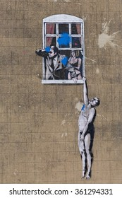 April 2014 - Bristol, United Kingdom: A graffiti of the artist Banksy, called Wall Hanger, a naked man hanging on to a window sill