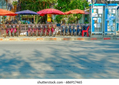 April 2017 Cha-am, Phetchaburi Province, Thailand Bicycle Rental for Tourists And the billboard attached to the telephone booth