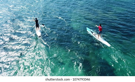 April 2018: Aerial photo of competition sport paddle surfing or sup between 2 men in tropical waters of Vouliagmeni beach, Athens riviera, Attica, Greece