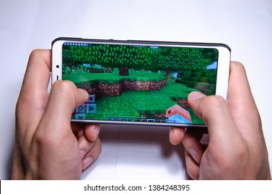 April 2019. Los Angeles, USA. Hands holding a smartphone with a game on the screen of Minecraft on a white background. Minecraft Pocket Edition gameplay. Minecraft mobile