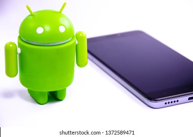 April 2019. Los Angeles,USA. Green plastic Android figure on a white background and with a smartphone. Figure, logo Android, Google