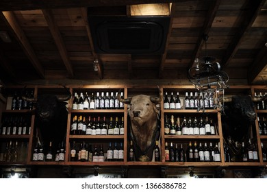 April 2019 - Seville Spain Typical Tapas restaurant interior with bottle of wine and stuffed bull head embalm
