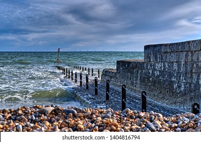 April 2019: A stone platform partially submerged on the Hove seafront. The pebble beach. It's a cloudy day but the sun casts a shadow onto the water. A wind farm can be seen on the horizon.
