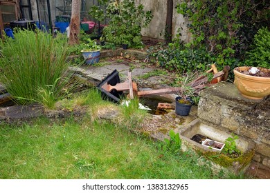 April 2019 - Traditional wooden bird table blown into a garden pond after  the storm has passed
