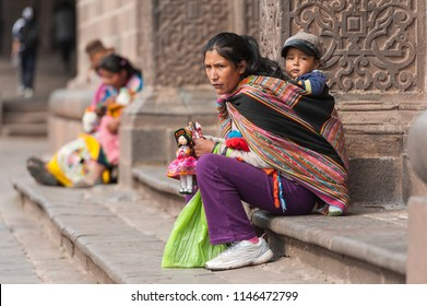 April 21, 2014 - Cusco, Peru. Indigenous woman selling handy-crafts with her young child. Wearing colorful traditional clothing in the Plaza de Armas city square.