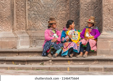 April 21, 2014 - Cusco, Peru. Group of indigenous women with young llamas. Wearing colorful traditional clothing and hats in the Plaza de Armas city square, on the steps of Church of La Compania.