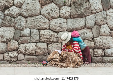 April 22, 2014 - Cusco, Peru. Poor indigenous woman with her baby. They are wearing colorful clothing in the city street.