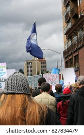 April 22 2017 Olympia WA USA Earth Day flag is carried proudly above the crowd as they move through downtown at the March for Science