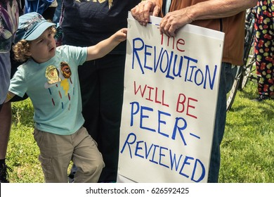April 22, 2017 SANTA ROSA, CA USA -Protester holds sign next to child about revolution during Earth Day's March for Science.