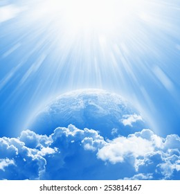 April 22 International Mother Earth Day, blue planet Earth in white clouds, bright sunlight from above. Elements of this image furnished by NASA nasa.gov