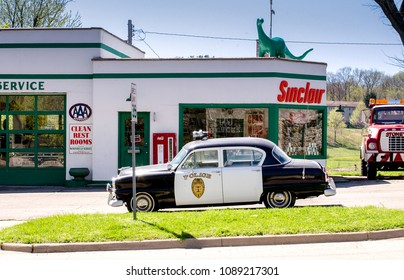 April 23 2017 Cassopolis MI USA; an old cop car sits in a retro still life outside an old Sinclair gas station from the 60's in  Cassopolis Michigan USA