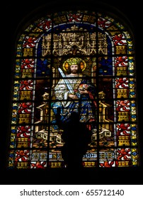 April 24, ,2017,  Seville Cathedral, Seville, Spain.  A vivid stained glass window of a crowned king.  There was a statue next to the window which casts a shadow on the window.