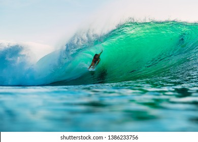 April 25, 2019. Bali, Indonesia. Surfer ride on barrel wave. Professional surfing with ideal ocean waves at Bingin beach