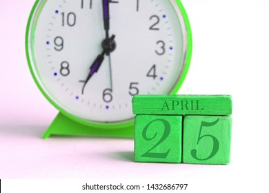 april 25th. Day 25 of month, handmade wood cube calendar and alarm clock on light green color. spring month, day of the year concept.