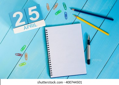 April 25th. International Day Of DNA. Image of april 25 wooden color calendar on blue background.  Spring day, empty space for text