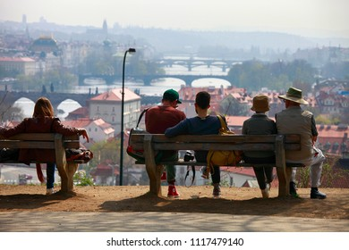 April 26, 2013, the Czech Republic, Prague. Tourists in Prague sit on a bench in a park with a view of the city