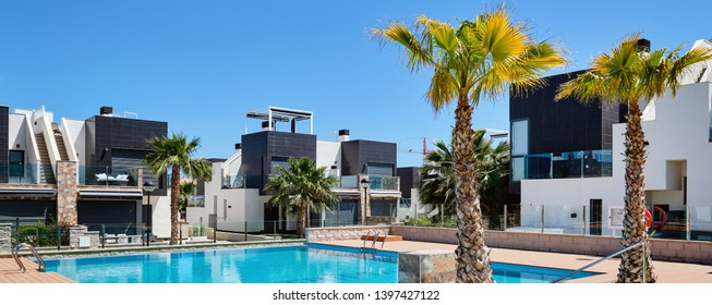 April 26, 2019: Panoramic view modern Spanish luxury villas with swimming pool at sunny day. Photo taken in Torrevieja resort city in Costa Blanca, Alicane, Spain. New property, loan, mortgage concept